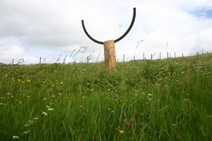 Wood and cast iron sculpture in field.
